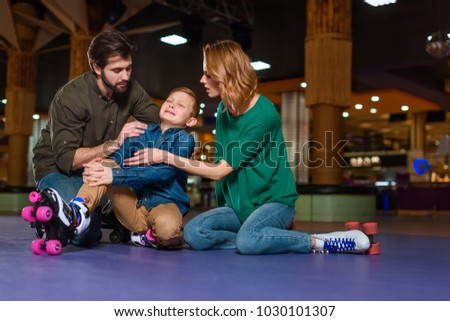 parents appeasing crying son in roller skates on roller rink