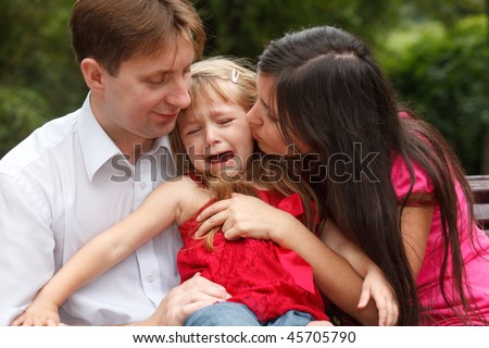 Parents calm crying girl on walk in summer garden. Girl sits in lap at father.