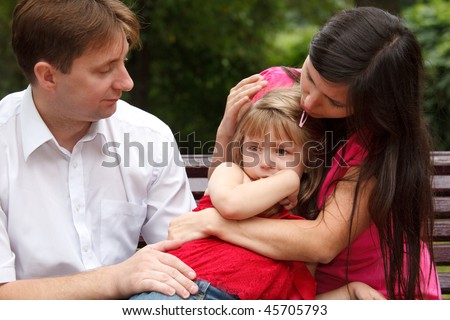 Parents calm crying girl on walk in summer garden. Mum embraces daughter.