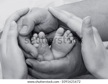 Parents care. Parents and child. Parents hands are gently hugging small foots of newborn.  #1091621672