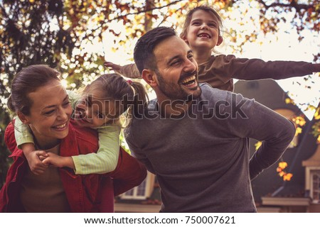 Parents carrying little girls on piggyback.