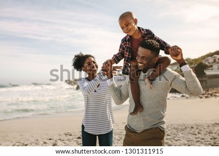 Parents carrying son on shoulders on beach vacation. African family of mother and father carrying son on his shoulders on vacation.