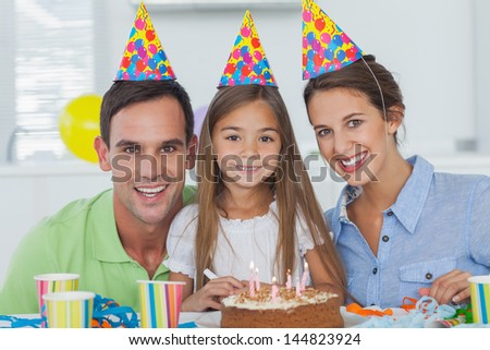 Parents celebrating their little girls birthday with a birthday cake