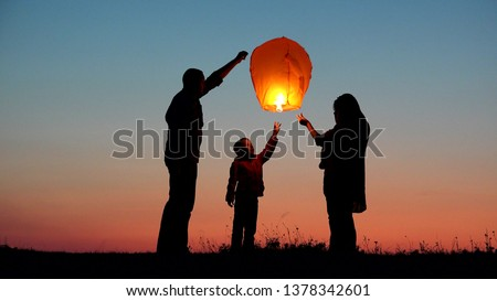 Parents, child and baby silhouette rising lightning sky lantern, release hope