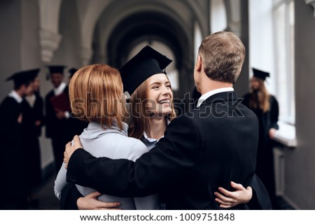 Parents congratulate the student, who finish their studies at the university. He graduates. They are very happy about this. #1009751848