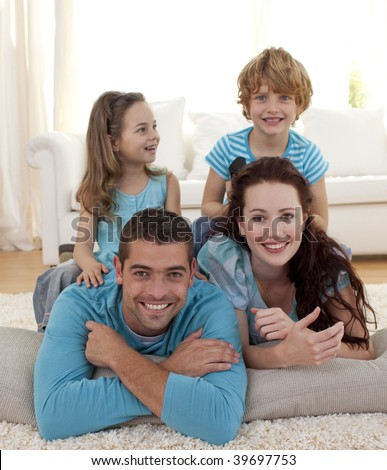 Parents, daughter and son lying on floor in living-room