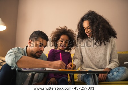 Parents drawing with their little girl.