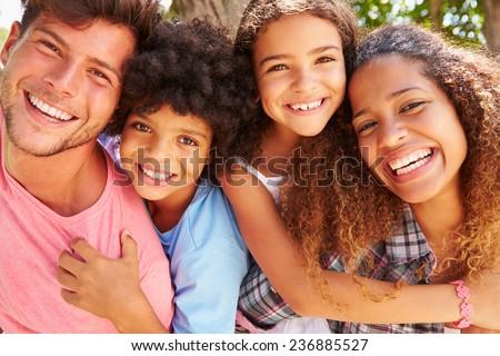 Parents Giving Children Piggyback Ride Outdoors