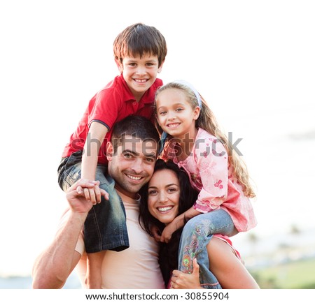 Parents giving children piggyback rides outdoors - stock photo