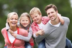 Parents Giving Children Piggybacks In Countryside