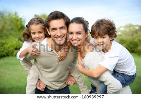 Parents giving piggyback ride to children