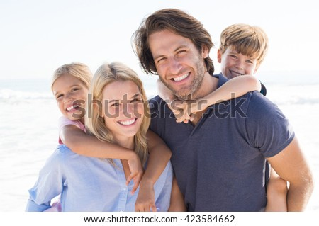 Parents giving piggyback ride to kids at beach. Close up of smiling family having fun at summer vacation. Portrait of happy family looking at camera at beach.  #423584662