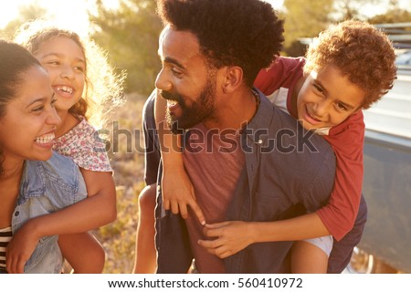 Parents giving their kids piggybacks, waist up, close up