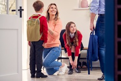Parents Helping Children In Uniform To Get Ready To Leave Home For School