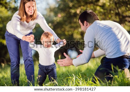 Parents holding their little son making first steps