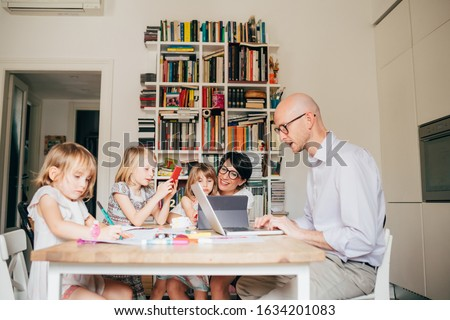 Parents indoor sitting table homeschooling with three female children - mentoring, teaching, education concept