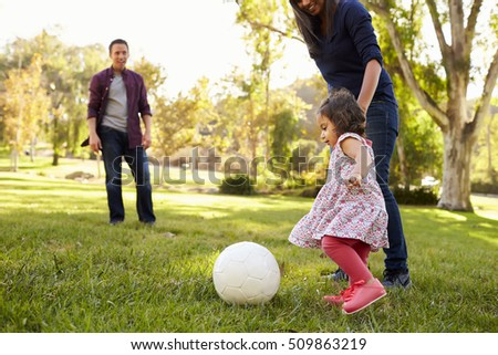 Parents kicking a ball with their young daughter in a park #509863219