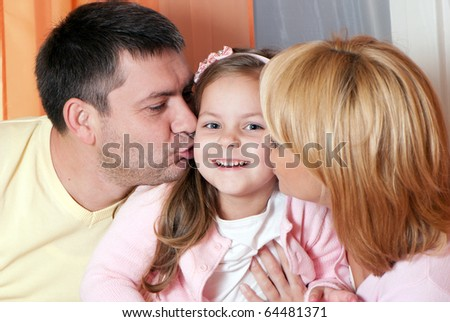 parents kissing daughter portrait looking very happy