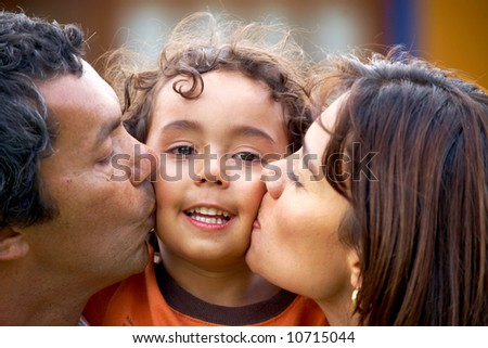 parents kissing their son and smiling