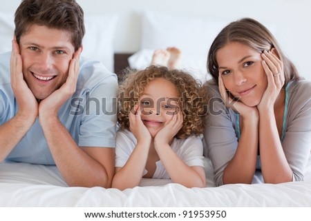 Parents lying on a bed with their son while looking at the camera