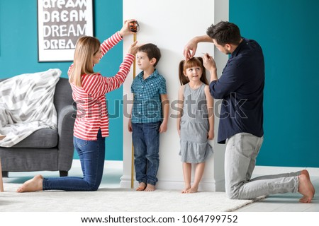 Parents measuring height of their children at home #1064799752