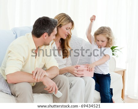 Parents offering a gift to her daughter on the sofa