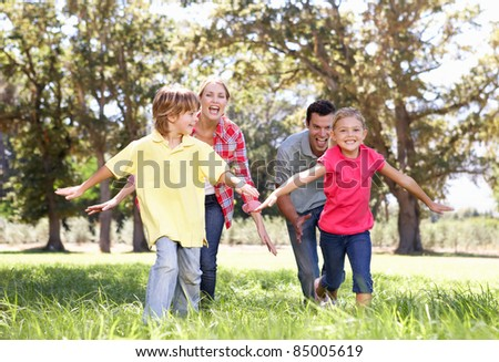 Parents playing with children in country