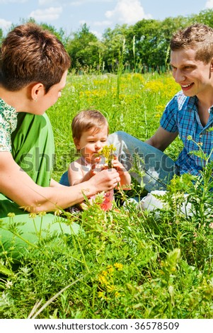 Parents playing with their daughter in the meadow - stock photo