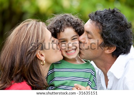 Parents proud of his son give him a kiss