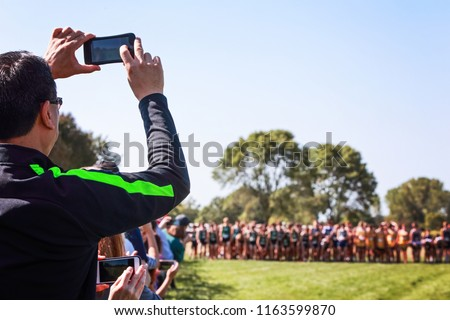 Parents recoding a cross country meet at the starting line