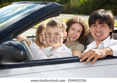 Parents sit with their children on their knees on front seats of gig, boy holds steering wheel.