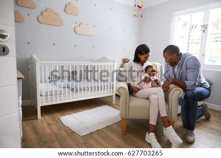 Parents Sitting In Nursery With Baby Daughter