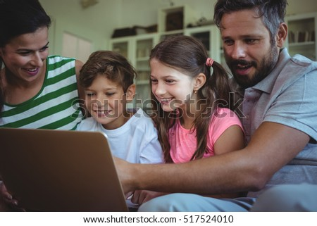 Parents sitting on sofa with their children and using laptop in living room at home #517524010