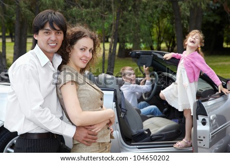 Parents stand near cabriolet slightly embraced, children play in the car and shout something loudly