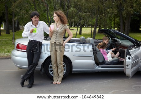 Parents stand near gig, talk and drink something from plastic cups, children play in the car - stock photo