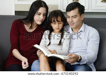 Photo of Parents teach books to their daughters at home. Kid reading book with farther and mother  on sofa at home on holiday . Image of family sitting on the sofa and spending free time at home