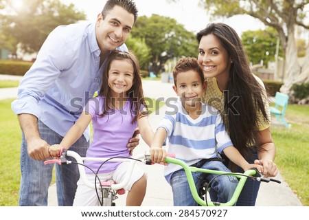 Parents Teaching Children To Ride Bikes In Park #284570927