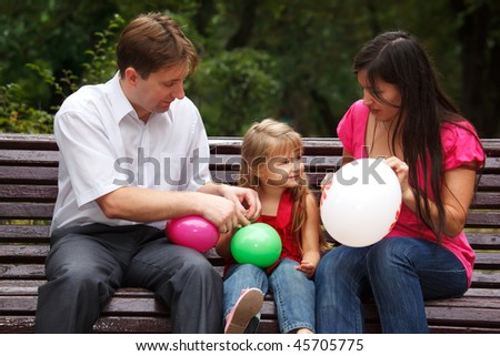 Parents together with daughter on bench in park in afternoon. In hands multi colored balloons.