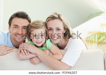 Parents together with daughter on the couch - stock photo