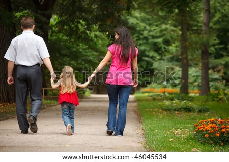Parents together with daughter walk on summer garden. Leave afar keeping for hands.