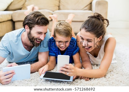 Parents using digital tablet and mobile phone in living room at home