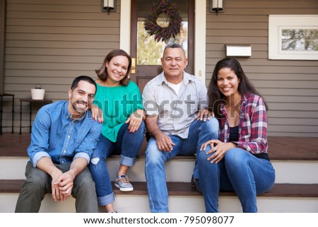 Parents With Adult Offspring Sitting On Steps in Front Of House #795098077