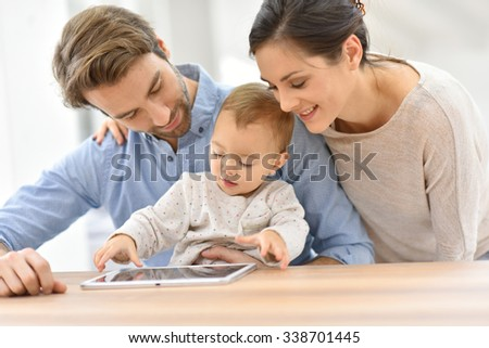 Parents with baby girl playing with digital tablet #338701445