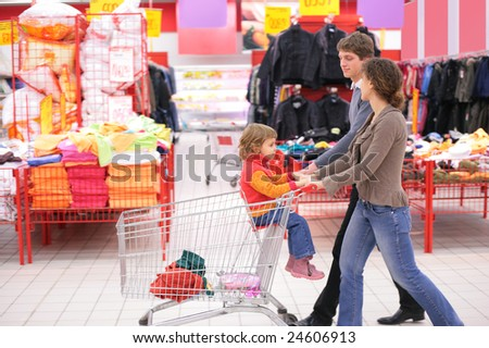 Parents with child in cart in supermarket