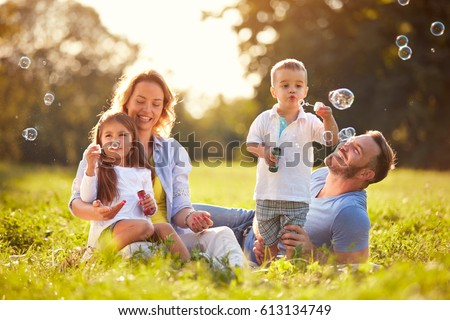Parents with children having fun in nature with soap bubbles