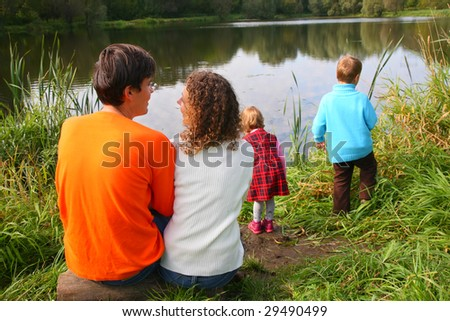 Parents with children sits on bank of pond, rear view