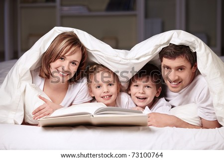 Parents with children under the blanket with a book