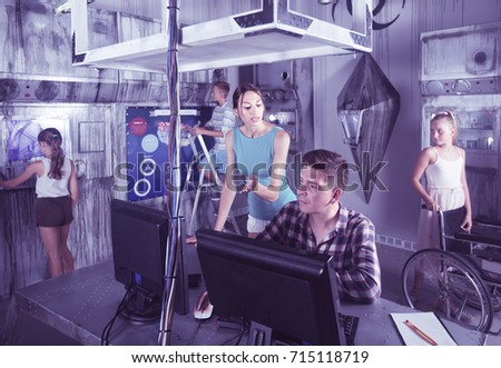Parents with kids are solving puzzles on computer in escape room stylized like laboratory.