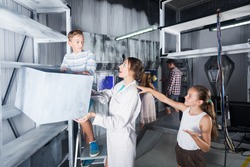 Parents with their children are visiting the escape room stylized under laboratory