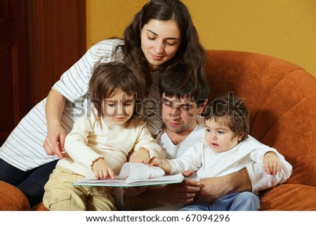 Parents with two daughters reading book sitting on sofa